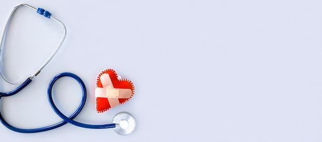 Bovenaanzicht van beschadigde hartvorm met een stethoscoop en kopieer de ruimte