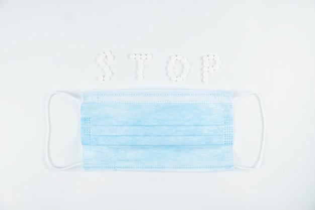 Bovenaanzicht van beschermend masker en woord stop geschreven met pillen. stop virus concept.