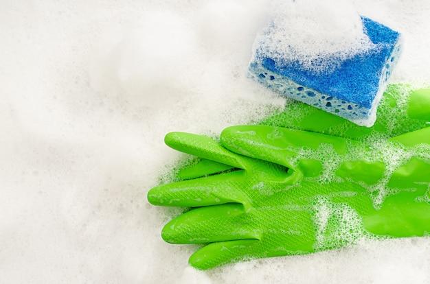 Bovenaanzicht van beschermende groene handschoenen en spons op zeepachtige achtergrond. huishoudelijk werk concept. kopieer ruimte, bovenaanzicht