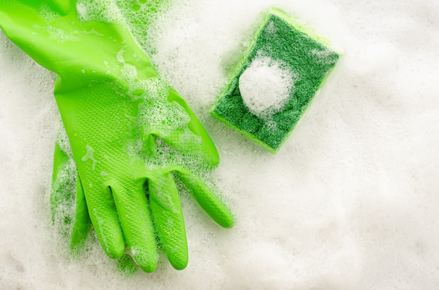 Bovenaanzicht van beschermende groene handschoenen en spons op zeepachtige muur. huishoudelijk werk concept. kopieer ruimte, bovenaanzicht