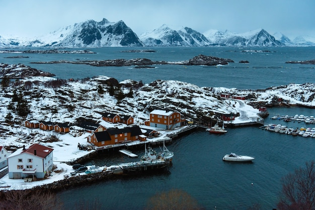 Bovenaanzicht van besneeuwd vissersdorp met ligplaats en veel boten. koude zeeweg en rotsachtige bergen rondom. prachtig uitzicht op de noorse natuur.