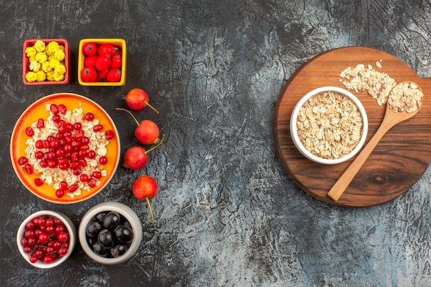 Bovenaanzicht van bessen havermout op het bord granaatappel snoepjes kleurrijke bessen