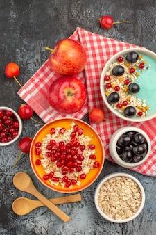 Bovenaanzicht van bessen lepels appels kleurrijke bessen havermout granaatappel