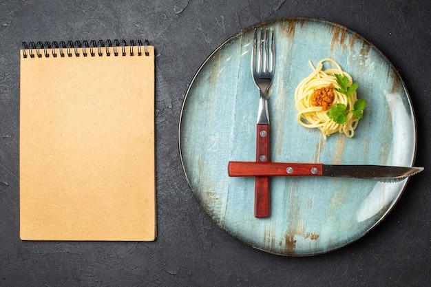 Bovenaanzicht van bestekset pastamaaltijd met vlees op blauw bord en notitieboekje op zwarte achtergrond met vrije ruimte