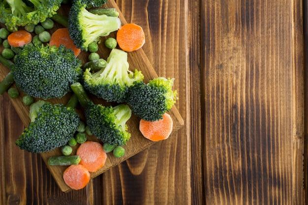 Bovenaanzicht van bevroren groenten op snijplank