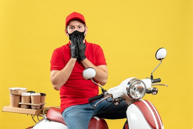 Bovenaanzicht van bezorgde jonge volwassene met rode blouse en muts handschoenen in medisch masker leveren bestelling zittend op scooter op gele achtergrond