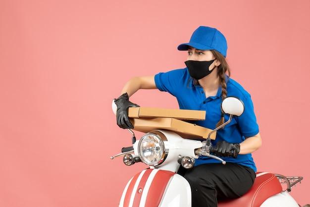 Bovenaanzicht van bezorgde vrouwelijke koerier met een medisch masker en handschoenen die op een scooter zitten en bestellingen afleveren op pastel perzik