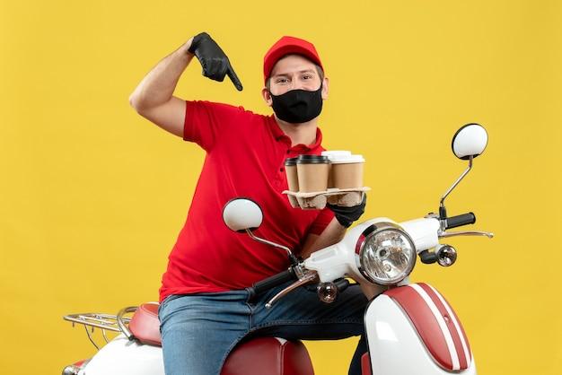 Bovenaanzicht van bezorger die uniform draagt en hoed handschoenen in medisch masker zittend op scooter met bestellingen die zich zelfverzekerd voelen