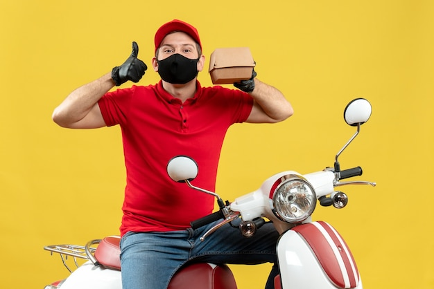 Bovenaanzicht van bezorger dragen rode blouse en hoed handschoenen in medische masker zittend op scooter volgorde met duim omhoog weergegeven
