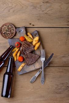 Bovenaanzicht van biefstuk en bier en aardappel