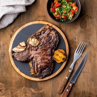 Bovenaanzicht van biefstuk op plaat met bestek en salade