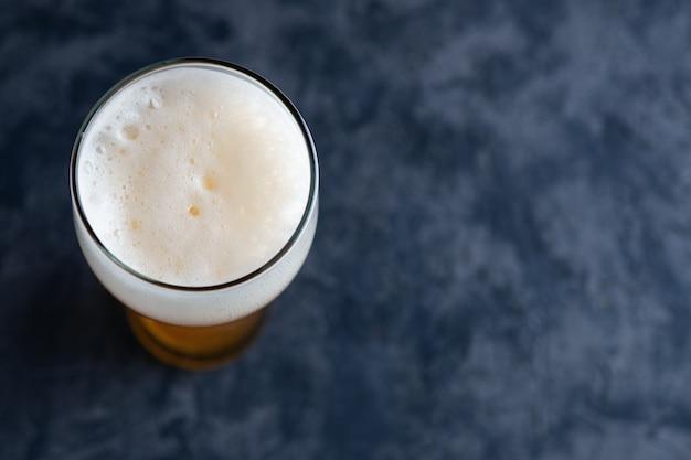 Bovenaanzicht van bierglas met schuim dop en copyspace