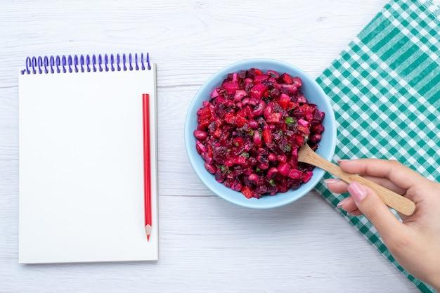 Bovenaanzicht van bietensalade gesneden met greens in blauwe plaat met blocnote op wit bureau, salade groente vitamine voedsel maaltijd gezondheid