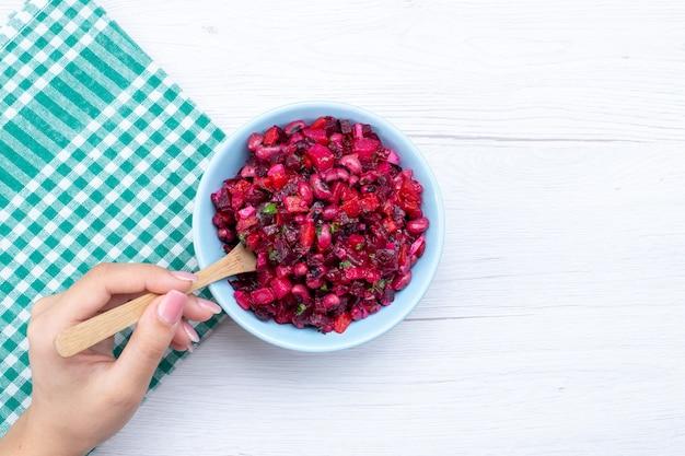 Bovenaanzicht van bietensalade gesneden met greens in blauwe plaat op licht bureau, plantaardige vitamine voedsel maaltijd gezondheidssalade