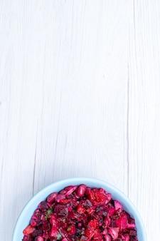 Bovenaanzicht van bietensalade gesneden met greens in blauwe plaat op licht, salade groente vitamine voedsel gerecht maaltijd gezondheid