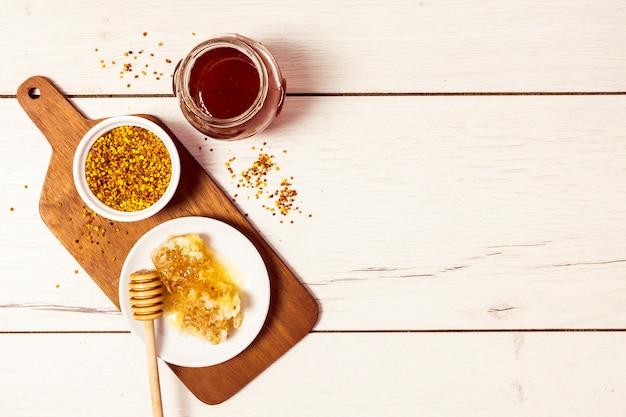 Bovenaanzicht van bijenpollen; honingraat en honing op witte houten textuur