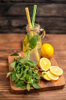 Bovenaanzicht van biologisch natuurlijk vers detoxwater geserveerd met buisjes munt en sinaasappel op een snijplank op een houten tafel
