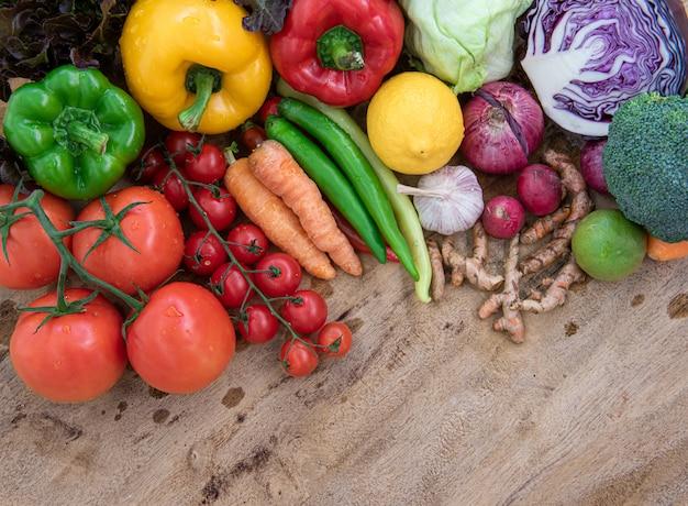 Bovenaanzicht van biologisch voedsel op houten bord, samenstelling met diverse rauwe biologische groenten