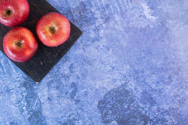 Bovenaanzicht van biologische appels op een houten bord over blauw.