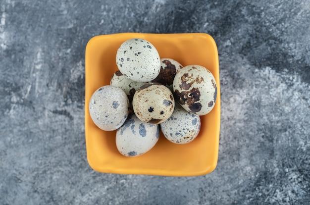Bovenaanzicht van biologische boerderij kwartel ei in gele kom.