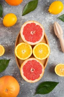 Bovenaanzicht van biologische citrusvruchten op een houten bord over grijze tafel.