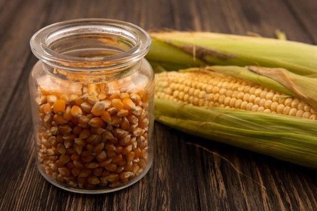 Bovenaanzicht van biologische en verse likdoorns met haar met maïskorrels op een glazen pot op een houten tafel