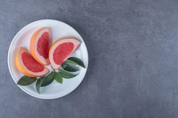Bovenaanzicht van biologische grapefruit plakjes en bladeren op een witte plaat.