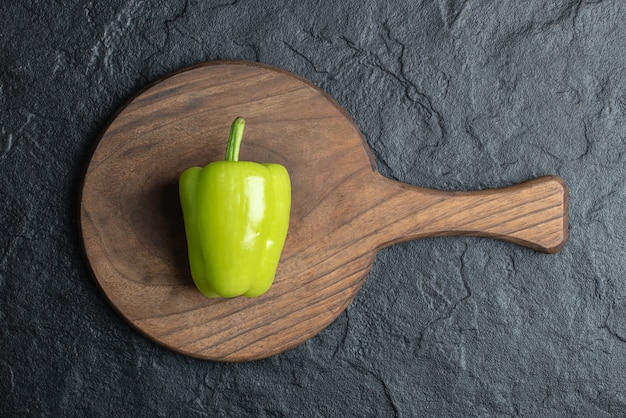 Bovenaanzicht van biologische groene peper op een houten bord op zwarte achtergrond.