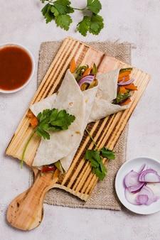 Bovenaanzicht van biologische groenten verpakt in pitabroodje met ui