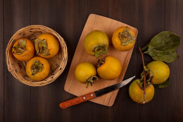 Bovenaanzicht van biologische kaki fruit op een emmer met kaki fruit op een houten keukenplank met mes op een houten tafel