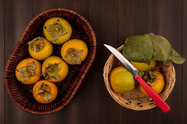 Bovenaanzicht van biologische kaki fruit op een emmer met mes op een houten tafel