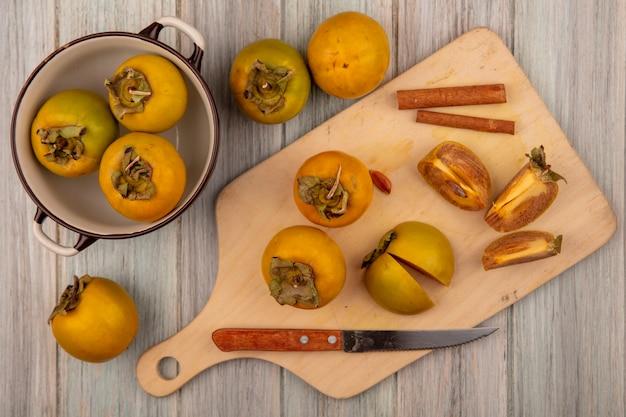 Bovenaanzicht van biologische kaki fruit op een houten keuken bord met kaneelstokjes met mes op een grijze houten tafel