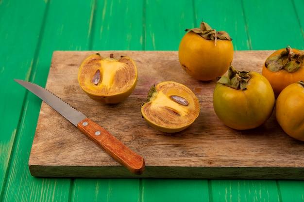 Bovenaanzicht van biologische kaki fruit op een houten keukenbord met mes op een groene houten tafel