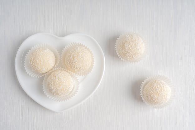 Bovenaanzicht van biologische kokostruffels geserveerd in hartvormige plaat op witte houten achtergrond