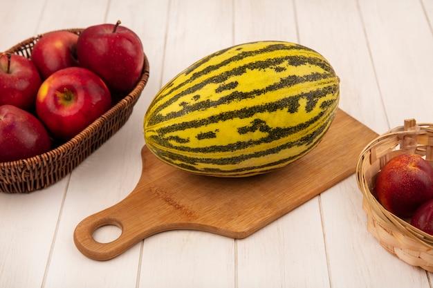 Bovenaanzicht van biologische meloen meloen op een houten keukenbord met appels op een emmer met perziken op een witte houten achtergrond