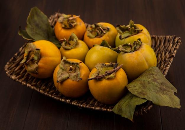 Bovenaanzicht van biologische onrijpe kaki fruit op een rieten dienblad met bladeren op een houten tafel