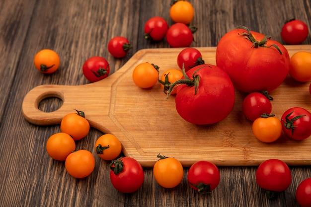 Bovenaanzicht van biologische oranje en rode tomaten geïsoleerd op een houten keukenbord op een houten oppervlak