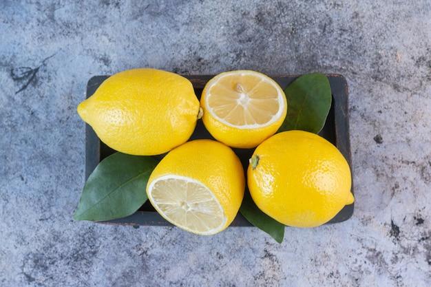 Bovenaanzicht van biologische sappige citroenen op houten plaat over grijs.