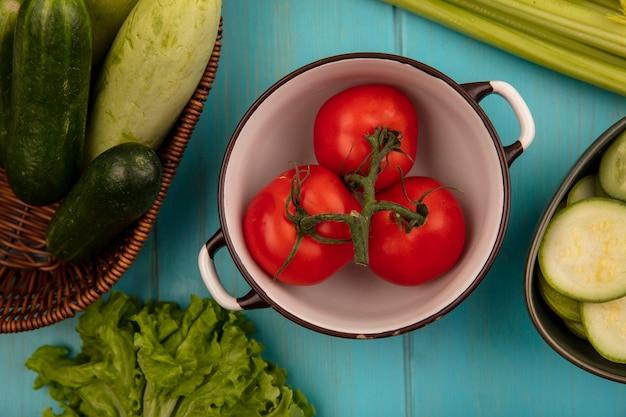 Bovenaanzicht van biologische tomaten op een kom met courgettes en komkommers op een emmer met sla en selderij geïsoleerd op een blauwe houten achtergrond