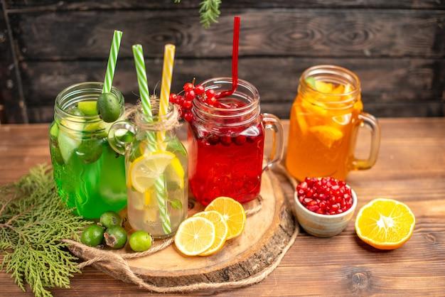 Bovenaanzicht van biologische verse sappen in flessen geserveerd met buizen en fruit op een houten snijplank op een bruine tafel
