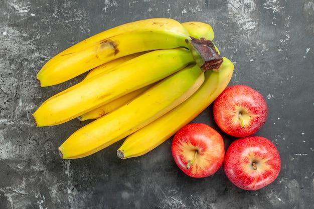Bovenaanzicht van biologische voedingsbron, verse bananenbundel en rode appels op donkere achtergrond