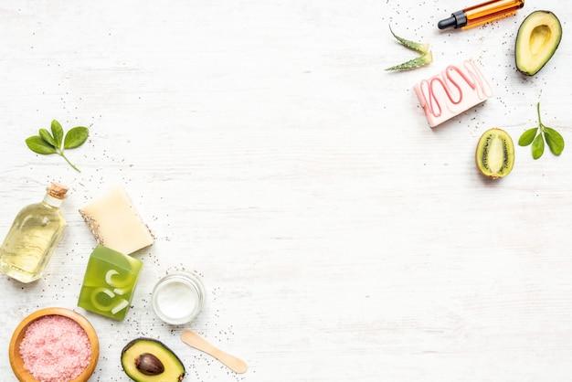 Bovenaanzicht van biologische zeep en cosmetica gerangschikt met fruit, kruiden, chiazaad, aloë en etherische oliën.