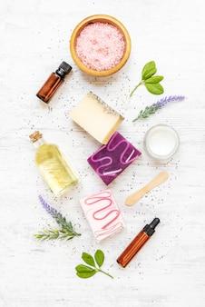 Bovenaanzicht van biologische zepen en cosmetica gerangschikt met lavendel, kruiden, chiazaden en etherische oliën.
