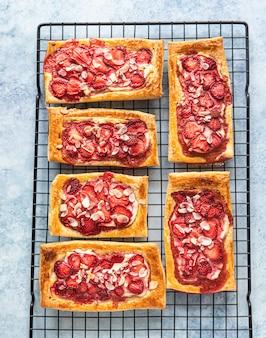 Bovenaanzicht van bladerdeeg mini taarten met roomkaas en aardbei versierd met amandel. blauwe betonnen achtergrond.