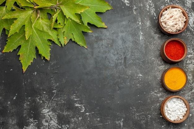 Bovenaanzicht van bladeren en kruiden op donkergrijze achtergrond