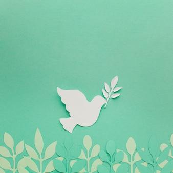 Bovenaanzicht van bladeren met papier duif en kopie ruimte