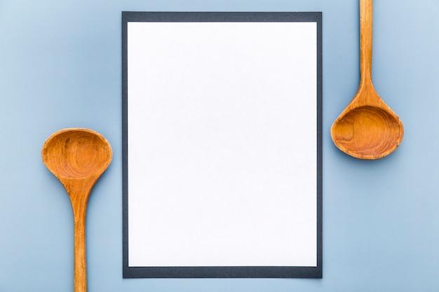 Bovenaanzicht van blanco menu papier met houten lepels