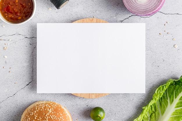 Bovenaanzicht van blanco menu papier met salade en broodje