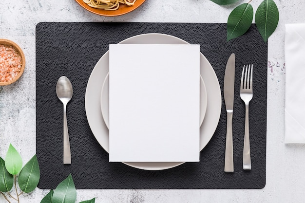Bovenaanzicht van blanco menu papier op plaat met bestek en bladeren