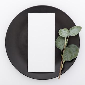Bovenaanzicht van blanco menu papier op plaat met plant